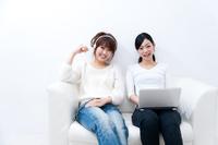 ソファーに座ってパソコンを操作する若い女性とヘッドホンで音楽を聴く若い女性