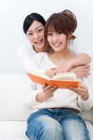 肩に腕をまわして本を見る仲良しの二人の若い女性