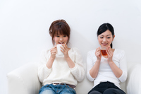 ソファーに座ってコーヒーブレイク中の二人の若い女性
