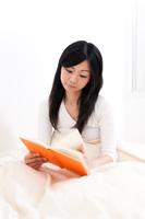 目覚めてベットの上で本を読むロングヘア―の若い女性