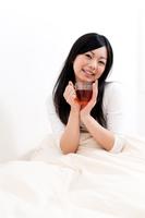 ベットの上で目覚めのお茶を飲むロングヘア―の若い女性