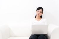 ソファーに座ってノートパソコンを操作する若い女性