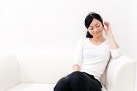 ソファーに座ってヘッドホンで音楽を聞く若い女性