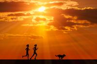 走る女性と犬に朝日