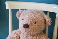 部屋の椅子に座っているクマのぬいぐるみ