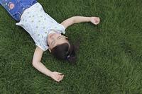 広い芝生の上で眠る女の子