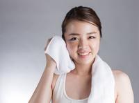 タオルで顔を拭う若い女性