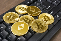 Bitcoin and Ethereum golden coins on a keyboard