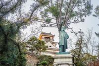 夕暮れの高知城と板垣退助像