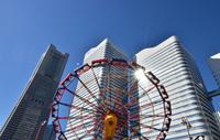 晴れた青空と都市の高層ビルと遊園地の回転遊具