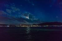 夜の海峡。対岸の街明かりと月と雲