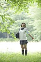 新緑の中で深呼吸をする女子高生