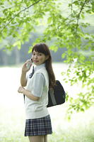 新緑の中で携帯電話を持つ女子高生