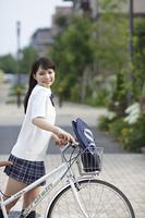 新緑の街の中の自転車を押す女子高生