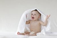 お座りをして頭にタオルをかけている外国人の赤ちゃん