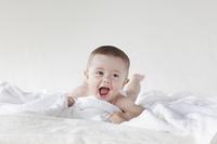 タオルの上に寝転がる外国人の赤ちゃん
