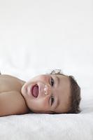 ベッドの上に寝転がっている外国人の赤ちゃん