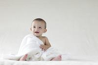 タオルをかけて座っている外国人の赤ちゃん