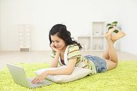 リビングで寝そべりパソコンをする若い女の子