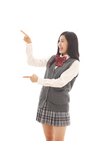 両手で指さしポーズをする女子高生