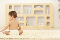 リビングで座る裸の赤ちゃん