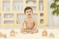 リビングで積木で遊ぶ裸の赤ちゃん