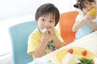 サンドイッチを食べる男の子ととうもろこしを食べる女の子