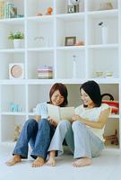 ノートを見る二人の女性と白い棚