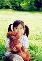 緑溢れる公園でプードルを抱く女の子