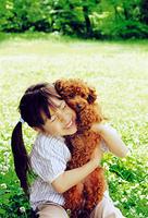 緑溢れる公園でプードルを抱きしめる女の子