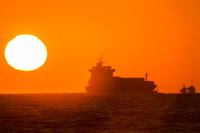 水平線上の日の出の太陽と船の影