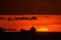 岬と日の出と横切る貨物船