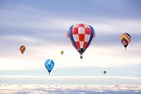 朝陽と雲海を背景に飛ぶ複数の熱気球。希望、夢、ノンビリ、スローイメージ