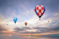 朝陽を背景に飛ぶ複数の熱気球。希望、夢、ノンビリ、スローイメージ
