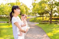 新緑の公園で女の子の赤ちゃんを抱く母。赤ちゃん、育児、幸せ、愛情、親子、絆イメージ
