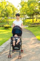 新緑の公園を背景にベビーカーを押し散歩をするす若い母。育児、子育て、赤ちゃん、教育、母子イメージ
