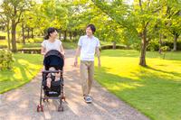 新緑の公園をベビーカーを押しながら散歩する若い夫婦。育児、幸せ、家族、新婚、愛情、絆イメージ