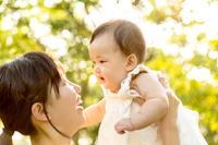 新緑の木漏れ日の下で赤ちゃんを持ち上げる若いお母さん。新緑、木洩れ日、親子、母子、娘、愛娘、愛情、幸せイメージ