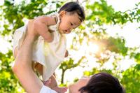 新緑の木漏れ日の下で赤ちゃんを持ち上げる若いお父さん。新緑、木洩れ日、親子、父子、娘、愛娘、愛情、幸せイメージ