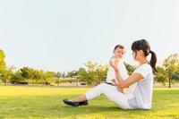 公園の新緑の芝生の上に座り一人遊ぶ女の子の赤ちゃん。育児、成長、健康、元気、子育て、赤ちゃんイメージ