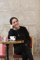 街角のカフェでくつろぐ外国人の若い女性