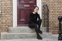 家の前に座る外国人の若い女性
