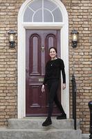 家の前に立つ外国人の若い女性