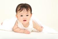 白バックの前に一人バスタオルで遊ぶ女の子の赤ちゃん。新生児、乳幼児、育児、子育て、健康、元気、成長イメージ
