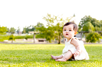 公園の芝生の上に座り一人遊ぶ女の子の赤ちゃん。育児、乳幼児、屋外、子育て、緑、幸せイメージ