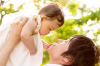 新緑の木漏れ日の下、赤ちゃんを高い高いするお父さん。育児、愛情、父子、親子、絆、幸せイメージ