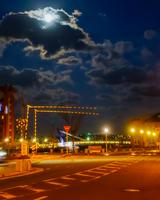 夜明け前の月が雲に隠れる空と港の踏切