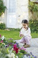 花がいっぱいの庭で遊ぶ女の子