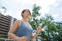 都会をランニングする若い女性