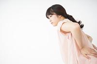 腰の痛みを感じる若い女性